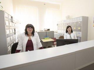 Dwie pracownice recepcji stoją za kontuarem i czekają na pacjentów